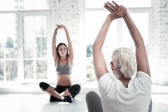 Retired lady training and stretching at fitness club. Active retirement. Selective focus on a turned back retired women lifting her hands and stretching while stock photo