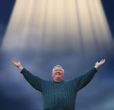 Retired at last. Newly retired man praising god with light beaming down Stock Photos