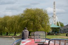 Combination of canal boat, big ferris wheel and bandstand in Stratford upon Avon during tourist season. Retired lonely man sat on bow of boat wearing grey jumper stock images