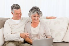 Retired lovers looking at their laptop Stock Photo