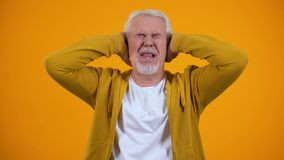 Retired male covering ears by palms displeased with gossips on orange background. Stock footage stock video footage
