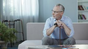 Retired male sitting on sofa at nursing home and thinking about life, sadness Stock Photography