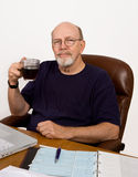 Retired Man Balancing the Checkbook. Senior man taking a coffee break while balancing his checkbook at his desk stock image