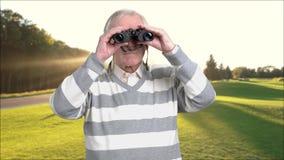Retired man with binoculars outdoors. Senior man looking through binoculars and enjoying beautiful landscape. Preparing for happy retirement stock video