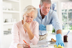 Retired man clearing up after breakfast Stock Photography