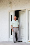 Retired man in the doorway of his home. Contented happy retired man standing in the doorway of his home with copyspace on white walls Royalty Free Stock Photography