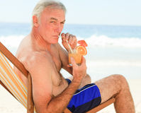 Retired man drinking a cocktail Stock Photo