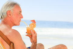 Retired man drinking a cocktail at the beach Royalty Free Stock Photography