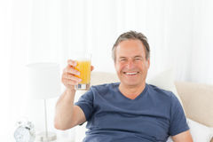 Retired man drinking oranje juice at home. Retired man looking at the camera while he is drinking oranje juice at home Royalty Free Stock Image