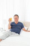 Retired man drinking oranje juice at home. Retired man looking at the camera while he is drinking oranje juice at home Royalty Free Stock Photos