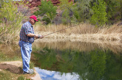 Retired Man enjoying a day of Fishing Stock Images