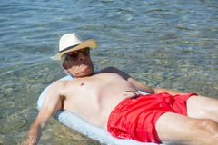 Retired man floating on bed in sea water Royalty Free Stock Photography