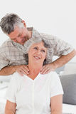 Retired man giving a massage to his wife. At home Royalty Free Stock Photography