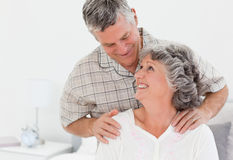 Retired man giving a massage to his wife. Retired men giving a massage to his wife at home Stock Image