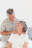 Retired man giving a massage to his wife. Retired men giving a massage to his wife at home Stock Photos