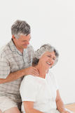 Retired man giving a massage to his wife. Retired men giving a massage to his wife at home Stock Images
