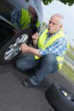Retired man has to change punctured wheel. Determined stock photos