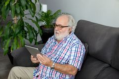 Retired man in his home. Retired man with white beard sitting on the sofa in his home Royalty Free Stock Photos