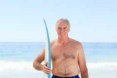 Retired  man with his surfboard Stock Images