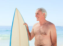 Retired  man with his surfboard Royalty Free Stock Images