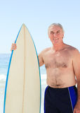 Retired  man with his surfboard. And looking the camera Stock Photo