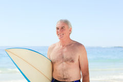 Retired  man with his surfboard. Behind the beach Stock Photos