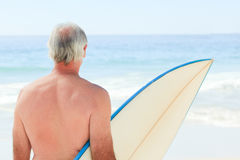 Retired  man with his surfboard Stock Photos