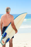 Retired man with his surfboard at the beach. Retired man posing with his surfboard at the beach Royalty Free Stock Photo