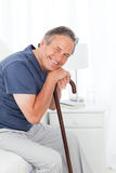 Retired man with his walking stick. On his bed Royalty Free Stock Images