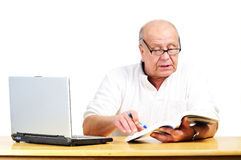 Retired man with a laptop. Retired senior learning on computer Royalty Free Stock Photo