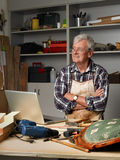 Retired man with laptop. Portrait of active retired carpenter sitting at his workshop in front of laptop and thinking. Small business Royalty Free Stock Images