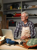 Retired man with laptop. Portrait of active retired carpenter sitting at his workshop in front of laptop and working. Small business Stock Image