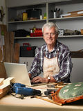 Retired man with laptop. Portrait of active retired carpenter sitting at his workshop in front of laptop and working. Small business Royalty Free Stock Images