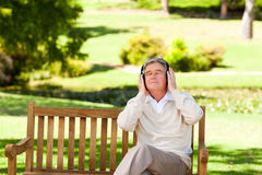 Retired man listening to some music. In a park Stock Images