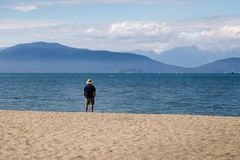 A retired man looking out at a beautiful view of the ocean and mountains on a sunny day. royalty free stock photos