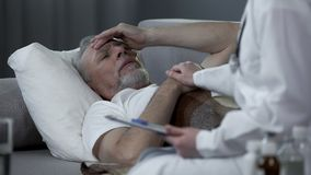 Retired man lying in bed and complaining doctor about headache, high temperature. Stock footage Stock Image
