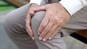 Retired man massaging knee, sitting on bench, inflammation of joints, trauma stock photography