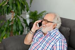 Retired man with a mobile in his home. Retired man with white beard and a mobile in his home Stock Images