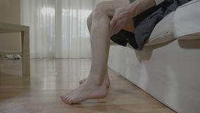 Retired man with muscular cramp sitting in bedroom rubbing his leg healing the unpleasant strain - stock footage