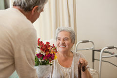 Retired man offering flowers to his wife Stock Photo