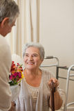Retired man offering flowers to his wife Royalty Free Stock Image
