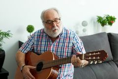 Retired man playing guitar. At home Stock Images