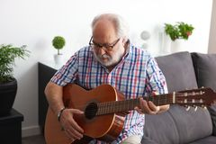 Retired man playing guitar Royalty Free Stock Images