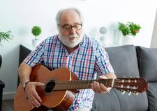Retired man playing guitar. At home Royalty Free Stock Photography