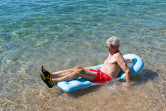 Retired man playing in sea water Stock Image