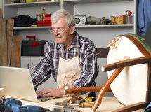 Retired man portrait. Portrait of retired manual worker sittiing in his small workshop in front of laptop and making online order. Small business Stock Image