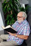 Retired man reading a book in his home Stock Photography