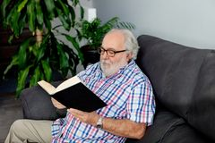 Retired man reading a book in his home Stock Photo
