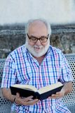 Retired man reading a book Royalty Free Stock Image