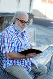 Retired man reading a book Royalty Free Stock Photo